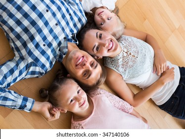 Portrait of happy relaxed family of four posing in domestic interior
