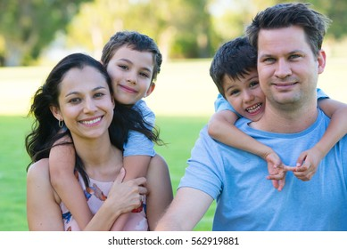 Portrait happy relaxed family in park outdoors, with young sons peeking, looking, smiling over shoulders from behind, blurred background.