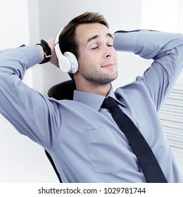 Portrait of happy relaxing businessman in headphones at office. Success in business concept.