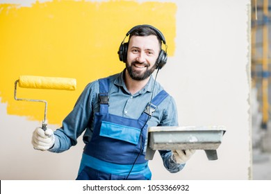 Portrait of a happy repairman listening to the music with headphones during the painting process indoors