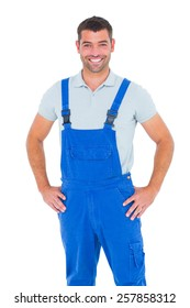 Portrait of happy repairman in overalls with hands on hip over white backgound