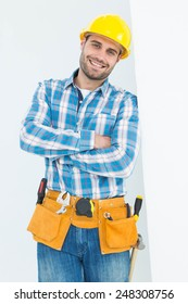 Portrait of happy repairman standing arms crossed on white background