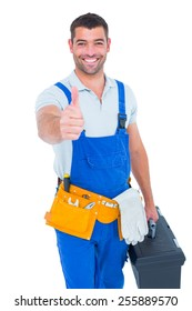 Portrait of happy repairman with toolbox gesturing thumbs up on white background
