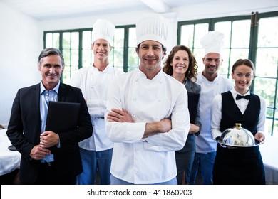 Portrait of happy restaurant team standing together in restaurant