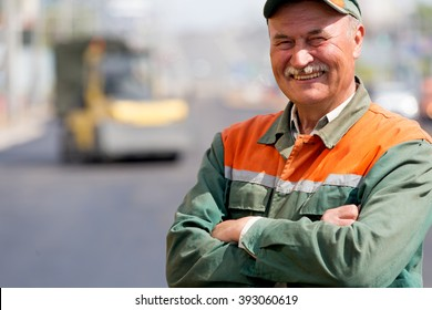 Portrait happy Road Worker on Asphalt Roller Machine background during Construction Resurfacing for driveways or Tarmac Repairing works