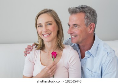 Portrait of a happy romantic couple with a flower at home