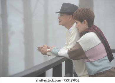 Portrait of happy romantic senior couple outdoor at the sea of fog