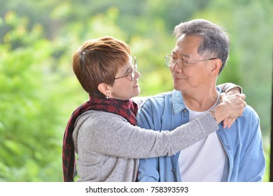 Portrait of happy romantic senior couple outdoor at the green nature background