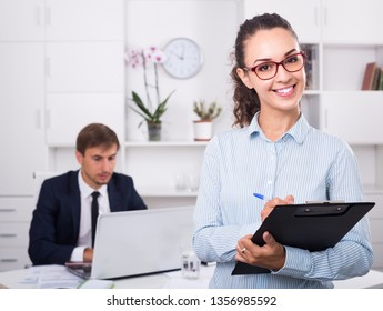 portrait of happy russian business woman holding cardboard in office