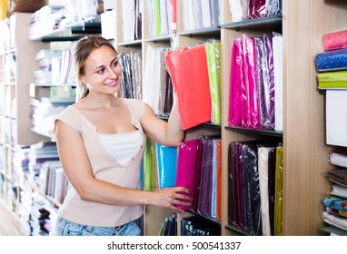 portrait of happy russian  female customer choosing tablecloths in home textile section in shop