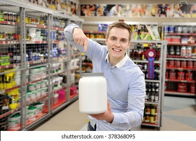 Portrait of happy salesman pointing finger at product in supermarket.