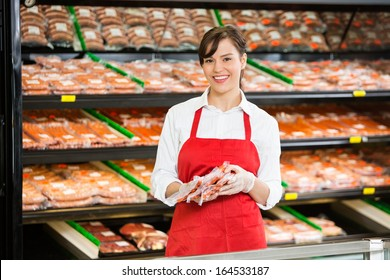 Portrait of happy saleswoman holding meat packages at counter in butcher's shop