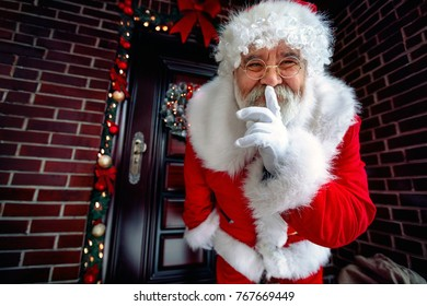 Portrait of Happy Santa Claus with finger on lips-Happy holidays