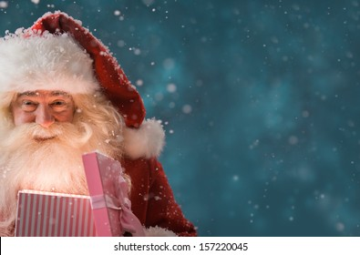 Portrait of happy Santa Claus opening gift box outdoors at North Pole. Magical light from box on his face