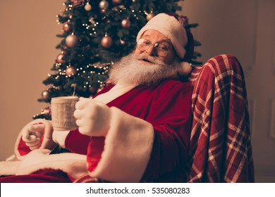 Portrait of happy Santa Claus resting at home and drinking tea