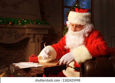 Portrait of happy Santa Claus sitting at his room at home near Christmas tree and answering Christmas letters.