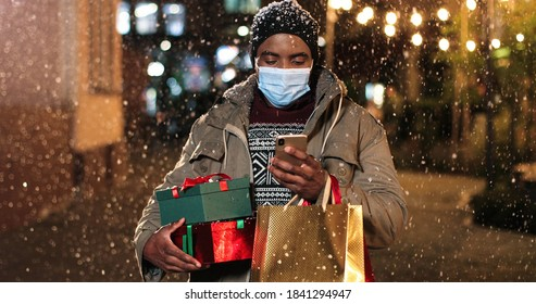 Portrait of happy satisfied African American man standing and texting on mobile phone while buying online. Male with shopping bags paying on smartphone with credit card while snowing. Presents concept - Shutterstock ID 1841294947