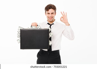 Portrait of a happy satisfied businessman holding briefcase full of money banknotes and showing ok gesture isolated over white background