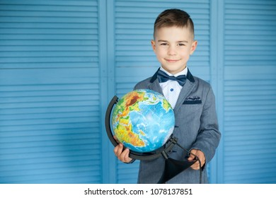 Portrait of a happy school boy in a costume with a globe. Back to school