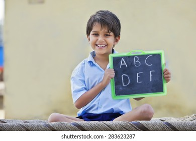 Portrait of a happy school boy holding slate with English alphabet on it