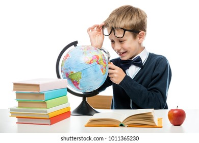 portrait of a happy schoolboy with a magnifying glass studying a globe against a white background