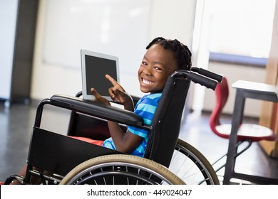 Portrait of happy schoolboy sitting on wheelchair and using digital tablet at school