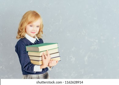Portrait of happy schoolgirl with books, isolated on grey background. Concept of education. School preschool. Day of knowledge. Children are our future. International children's book day.
