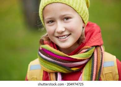 Portrait of happy schoolgirl looking at camera outside