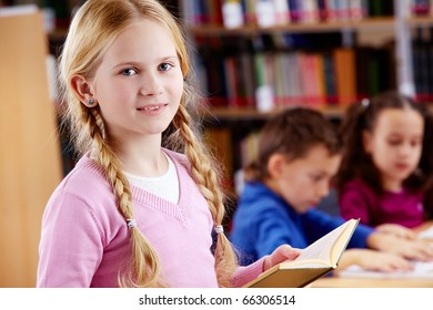 Portrait of happy schoolgirl with open book looking at camera in library