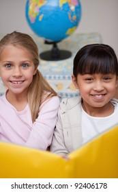 Portrait of happy schoolgirls reading in a classroom