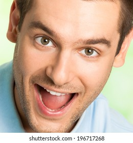 Portrait of happy screaming or laughing attractive young man, outdoors