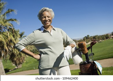 Portrait of happy senior African American woman with golf bag at golf course