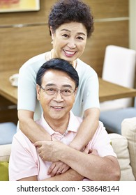 portrait of a happy senior asian couple looking at camera smiling.