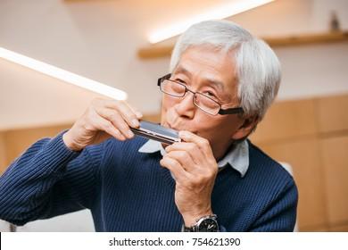 portrait of happy senior asian man playing harmonica