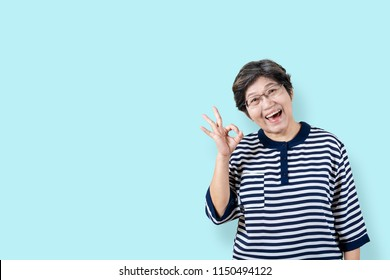 Portrait of happy senior asian woman gesture or showing hand ok and looking at camera on isolated background feeling positive enjoy and satisfaction. Older female lifestyle concept with clipping path.