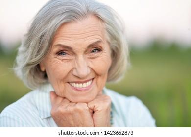 Porträt einer glücklichen älteren schönen Frau, die im Frühlingspark steht