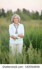 Portrait of happy senior beautiful woman posing in spring park