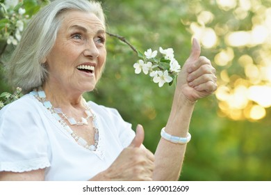 Portrait of happy senior beautiful woman in spring park showing thumb up