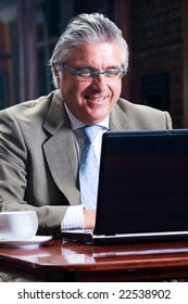 Portrait of a happy senior business man sitting by his laptop