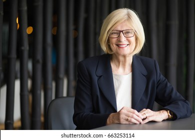 Portrait of Happy Senior Business Woman at Table