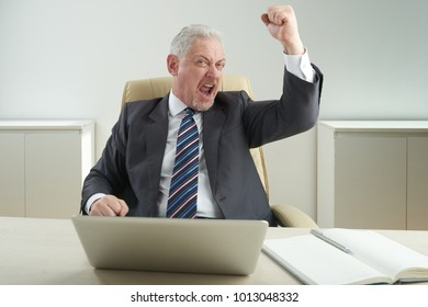 Portrait of happy senior businessman wearing classical suit sitting at office desk and showing yes gesture, interior of office on background