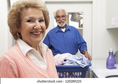 Portrait of a happy senior couple in bathroom washing clothes