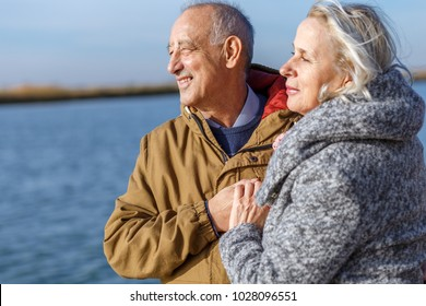 Portrait of happy senior couple by the lake on sunny autumn day.