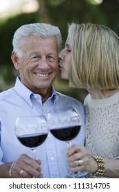 Portrait of happy senior couple celebrating while wife kissing husband on cheek