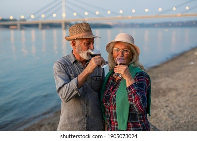 Portrait of a happy senior couple drinking wine and enjoying the sunset on the river.