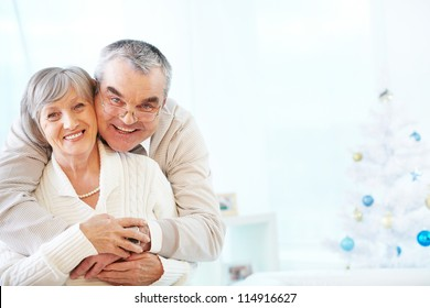 Portrait of a happy senior couple embracing and looking at camera