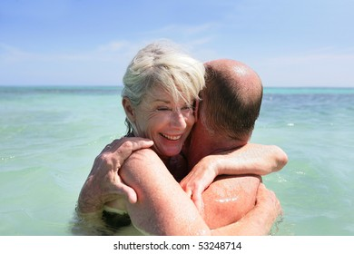 Portrait of a happy senior couple embracing in the sea