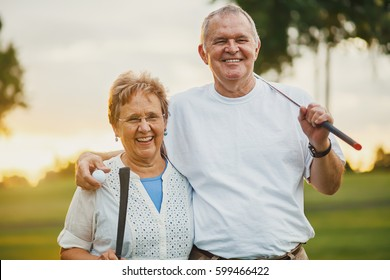 portrait of happy senior couple enjoying active lifestyle playing golf