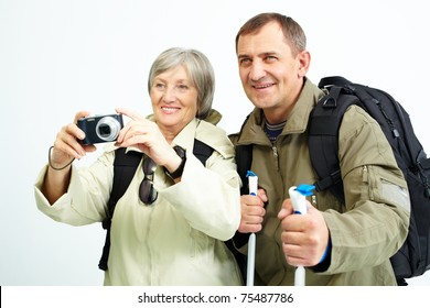 Portrait of happy senior couple going to take photo of something during trip