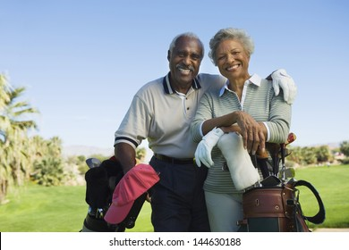 Portrait of happy senior couple in golf course smiling